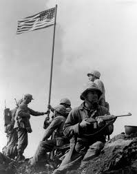 First flag raising over Iwo Jima. Louis Charles Charlo, from the Bitterroot Salish Tribe holds the rifle.