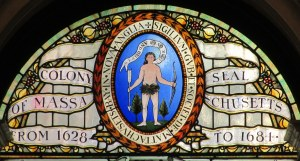The first official seal of the Colony of Massachusetts, shown in a stained glass window in the Massachusetts State House.